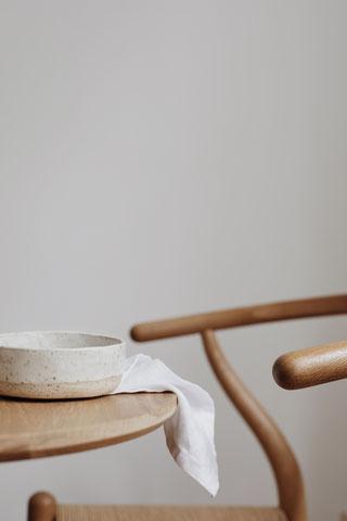 runder Holztisch mit Keramik und Leinentuch und Wishbone Chair