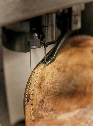 Hier wird die plangeschliffene Originalsohle mit der Durchnähmaschine angenäht. Die Laufsohle wird anschließend aufgeklebt, um das direkte Eindringen von Wasser in den Schuh zu verhindern.