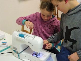 Kinder beim Nähen an einer Nähmaschine in der Nähwerkstatt Handgemacht in Bielefeld