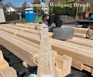 Blockhausbau - Blockhaus bauen - Massivholz - Formstabile Lammellenbalken  - Baustelle - Neubau - Gießen - Marburg - Holzbau - Hausbau - Holzbauweise - Offenbach - Hanau - Fulda - Zimmerei - Holzhaus - Zimmermann bei der Arbeit - Blockhausmontage