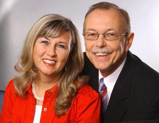 Autor und Verlegerin der Musikkalender: Links im Bild ist eine Dame mit blondem offenen Haar, rechts ein Mann mit Brille und Schnauzbart mit schwarzem Jacket, weißem Hemd und Krawatte. Beide lächeln zur Kamra. Renate Bach, links, hat eine rote Bluse an.