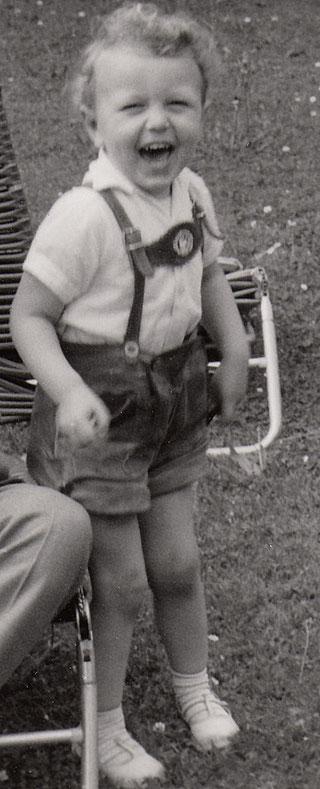 Der Autor der Musikkalender als kleiner Junge. Es ist ein schwarz/weißes Bild. Peter BAch jr. hat kurze Lederhosen an und strahlt zur Kamera. auffällig ist der blonde Lockenkopf.