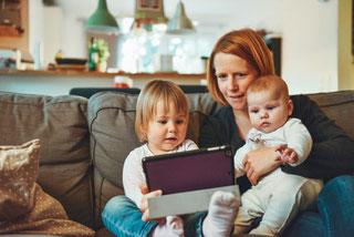 Enfant en Visio consultation sur tablette au côté de sa maman