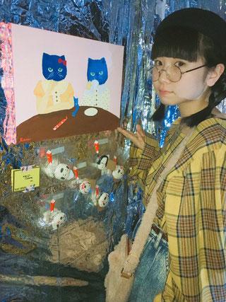 擬人化された青色の顔の猫の絵とおかめブローチ。アヴァンギャルドな色使いだ。赤いリボンはリルガリボンだろうか。