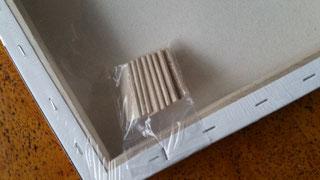 Een deel van schildersdoek van de Action, met daarin een zakje spielatjes, platte houten miniplankjes om het doek op spanning te maken.
