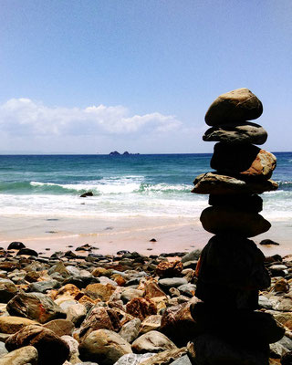 pile of rocks in front of the sea ocean in a bay at the walkway of the byron bay lighthouse in australia