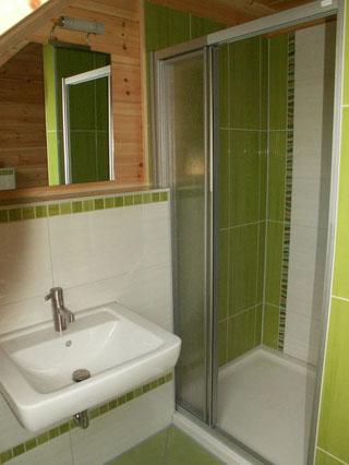 Gästebad im Blockhaus mit grüner Mosaik-Bordüre - © Blockhaus-Profi