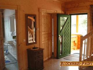 Eingangsbereich im Blockhaus mit grünen Details - © Blockhaus-Profi