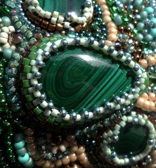 photo détail d'un cabochon en malachite, pierre fine verte, brodé de perles ivoire vertes et bleues sur un bracelet manchette