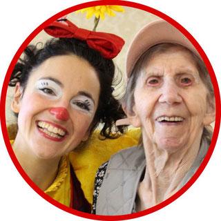 Bewohnerin einer Pflegeeinrichtung freut sich über den Besuch der Clownin