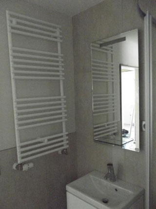Die ecke eines Badizimmers mit modernem Waschbecken und Heizkörper mit Handtuchhalter