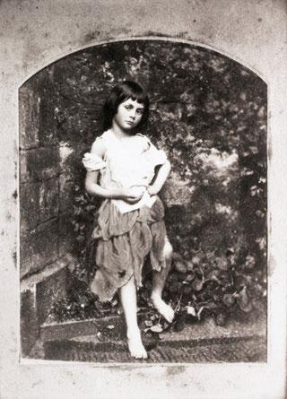 乞食のファッションを身につけたアリス。裂けた服の方を落とし、やや悩ましげなポーズを取っている。チャールズ・ドッジソン撮影