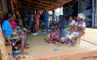 Impftag für Kleinkinder: Frauen warten mit ihren Kindern im Schatten der Gesundheitsstation