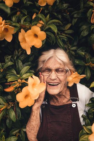 Alte Frau lachend mit Blumen im Haar