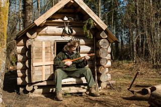 John C jouant de la dombra, devant une isba qu'il a construit en 2011