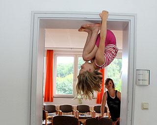 Ein Kind hockt kopfüber in einem Türrahmen.