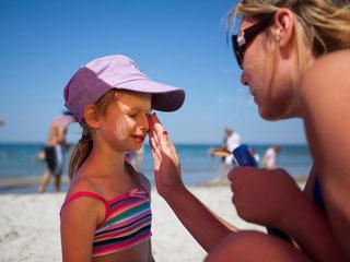Ein Klecks Sonnencreme ist nicht genug: Besonders am Strand reflektiert das Licht. Deshalb sollten Eltern den Sonnenschutz dick und mehrfach auftragen. Foto: Silvia Marks