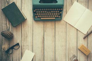 Schreibmaschine auf Holzplatte; rechts daneben ein Buch; links unten eine Brille; Schreibmaschine im Mittelpunkt