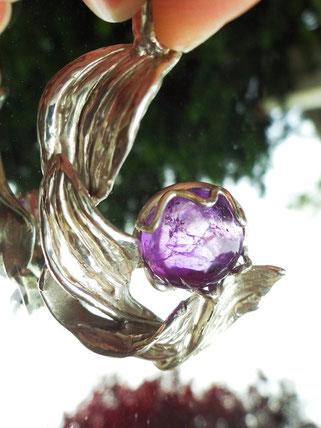 Un pendentif avec des feuilles sculptées en argent a en son centre une très belle améthyste violette.
