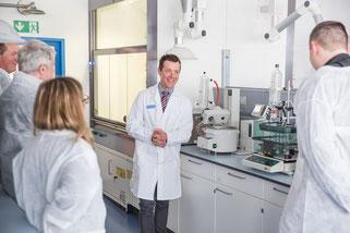 Laborleiter Wojciech Krawczyk erläutert bei einer Laborführung die Funktionen der Geräte