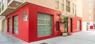 Fachada de color rojo de nuestra consulta de podología en Murcia, con la que damos servicio al barrio del Carmen en C/ Jumilla, Murcia