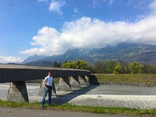 Auf der alten Rheinbrücke in Vaduz. Noch befinde ich mich auf liechtensteinischem Boden. Nach passieren der Holzbohlen, unter denen recht lautstark der schmale Rhein dahinfließt, stehe ich auf schweizerischem Territoriom.