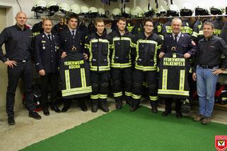 Vertreter der Lieferfirma (jeweils außen) mit den Führungskräften der Freiwilligen Feuerwehren aus Ascha und Falkenfels bei der Übergabe der neuen Schutzkleidung im Gerätehaus der Feuerwehr Falkenfels