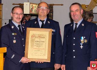 Vorstand Richard Marchner (links) und Kommandant Herbert Heindl (rechts) überreichen die Ehrenurkunde an Ludwig Stahl