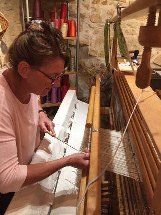 tisserande florence Bibollet à l'enfilage sur un métier à tisser 4 cadres