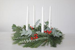 Adventskranz mit Eukalyptus und roten Beeren mit weißen Kerzen