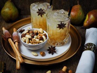 Alkoholischer Aperitif, gesalzene Nüsse und Crissini mit Parmaschinken