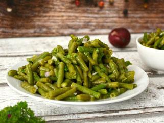 Grüner Bohnensalat auf Teller mit Zwiebel und Petersilie