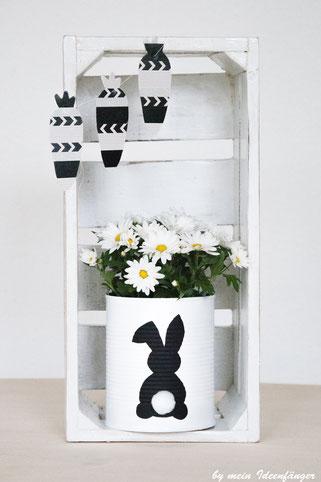 Schöne Upcycling-Idee zu Ostern: Mit Hase verzierte Blechdose im Weinkorb