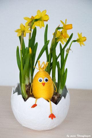 Deko zu Ostern: Küken auf einer mit Narzissen bepflanzten Gipsschale