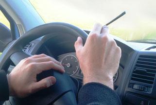 Hände am Steuerrad beim Autofahren mit CBD Joint in der Hand