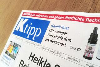 Titelseite von Ktipp artikel mit CBD Ölen im Test auf Holztisch liegend
