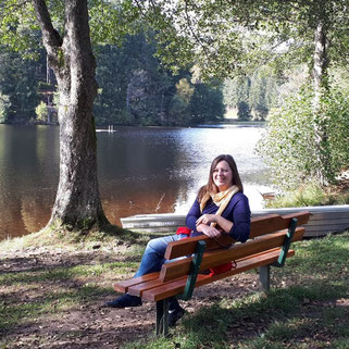 Sonja Kleiser auf einer Parkbank am See