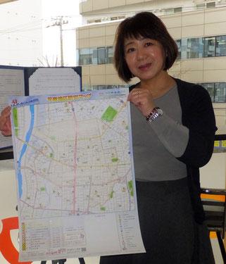 地域住民手作りの防災マップを掲げる塚本薫さん