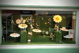 frühlings-Schaufenster mit Geschenkartikeln, ganz in Rasen mit weißen Blüten