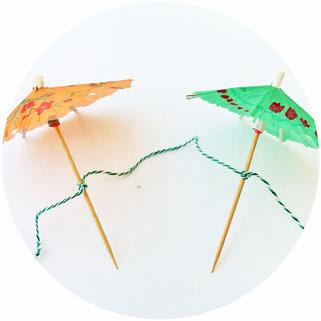 Bild: DIY Deko Girlande für die Party oder Hochzeit aus Cocktailschirmchen als Hintergrund für eine Fotoecke selber machen; Anleitung und Tipps vom DIY Deko und Partystyling Blog  www.partystories.de