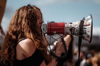 woman speaking through a megaphone during a public event.