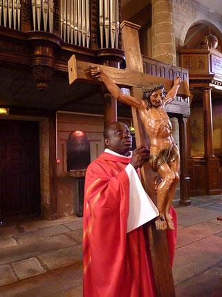 P. Yves TANO remonte l'allée centrale, avant de poser la croix devant l'autel