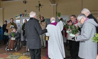 Traditionnellement, la bénédiction des rameaux se déroule à l'extérieur de l'église, comme ici à Pleyber depuis le préau de l'école St Pierre. La procession rejoint ensuite à pied l'église toute proche.