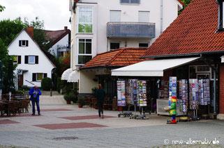 Sälzerplatz in Bad Sassendorf mit Häusern, Menschen und Geschäften.