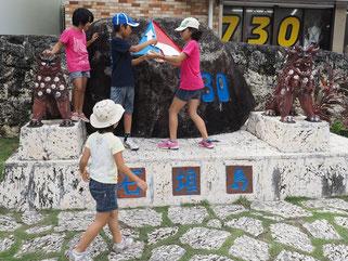 730記念碑のペンキ塗り替えを行う子どもたち=30日午後、同交差点
