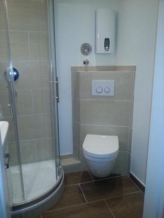 Ein Badezimmer mit Toilette und Duschkabine