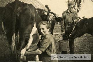 Twee  koeien met een melkende boerin en boeren zoon. Zwart-wit foto.