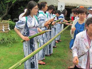 笹の葉柄の浴衣着た「笹娘」による笹酒のふるまい