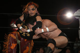 Shimizu delivers a submission hold to his opponent.