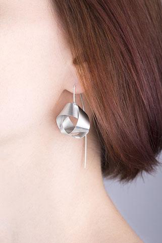 Ein raffiniert mit sich selbst verschlungenes Silberband bildet das zentrale Element der Ohrhänger NOLA. Ihre klare Eleganz und das seidig matt und geheimnisvoll schimmernde Silber machen NOLA unwiderstehlich. Die Ohrhänger sind wunderbar schwerelos